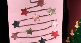Postal de Navidad con lana vieja y estrellas de cápsulas nespresso