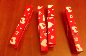 Pinzas de madera pintadas de rojo con corazones blancos
