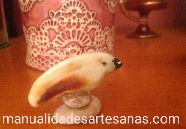 Adorno de pájaro hecho con piedras y trozo de concha marina