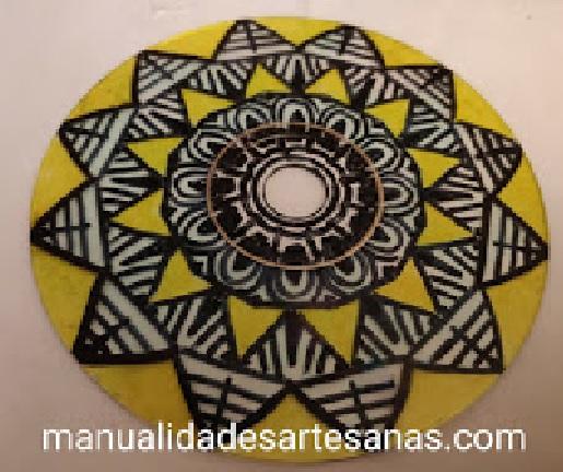 Dibujo de mandala con triángulos pintado en un cd viejo