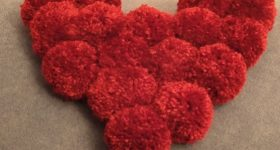 Cojín forma corazón de pompones de lana vieja para San Valentín